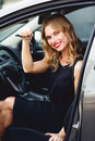 Elegant smiling woman in black dress in car holding keys Royalty Free Stock Photo