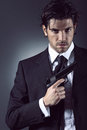 Elegant spy portrait and handsome posing with gun in hand grey backdrop Stock Images