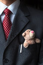 The elegant stylish businessman keeping cute Teddy bear in a his breast suit pocket. Formal negotiations concept.