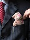 The elegant stylish businessman keeping cute teddy bear in a his breast suit pocket. Hand shaking teddy bear's paw. Formal n