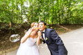 Elegant stylish groom and happy gorgeous  bride have fun with bubble blower outdoors in park Royalty Free Stock Photo