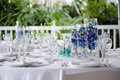 Elegant table setting details of an banquet with lush greenery in the background Royalty Free Stock Photo