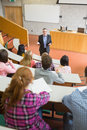 Elegant teacher with students at the lecture hall sitting college Royalty Free Stock Images