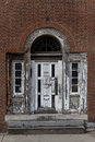 Elegant, weathered white door with ornate details on rustic brick wall