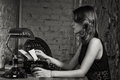 Elegant woman in black with the old typewriter at table Stock Photography