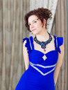 Elegant woman in blue dress portrait of stylish and elaborate necklace looking relaxed Royalty Free Stock Photos
