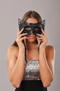 Elegant woman holding a masquerade mask isolated over grey background Stock Photo