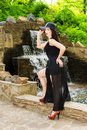 Elegant woman in park young beautiful a hat and a black dress near fountain Royalty Free Stock Photo