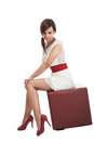 Elegant woman posing on a leather seat in stylish miniskirt and stilettos looking demurely down at the floor isolated white Royalty Free Stock Photography