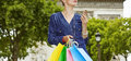 Elegant woman with shopping bags holding smartphone, Paris Royalty Free Stock Photo