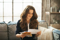 Elegant woman is sitting on couch and reading correspondence young with brown hairs in loft apartment Stock Images