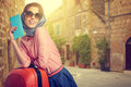 Elegant woman on street of italian city with a suitcase travel Royalty Free Stock Images