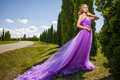 Elegant woman in violet long dress against of green alley Royalty Free Stock Photo