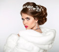 Elegant woman in white fur coat. Wedding Hairstyle. Beautiful fa Royalty Free Stock Photo