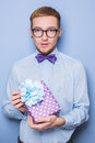 Elegant young man with colorful gift present birthday valentine studio portrait over blue background Stock Photos
