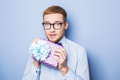 Elegant young man with colorful gift present birthday valentine studio portrait over blue background Royalty Free Stock Photo
