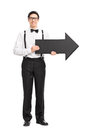 Elegant young man holding a big black arrow full length portrait of with bow tie and suspenders pointing right isolated on Royalty Free Stock Photos