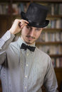 Elegant young man wearing top hat and bow tie attractive looking at camera indoors shot Stock Images
