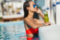 Elegant young woman in the pool with a cocktail. Royalty Free Stock Photo
