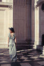 Elegant young woman standing in a grand hall Royalty Free Stock Photo
