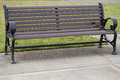 Elegantly designed empty wooden park bench grass behind Royalty Free Stock Photos