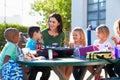 Elementaire leerlingen en leraar eating lunch Royalty-vrije Stock Afbeeldingen
