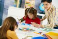 Elementary age children sitting around desk enjoying painting colors art class primary school classroom Royalty Free Stock Image