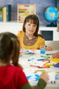 Elementary age children sitting around desk enjoying painting colors art class primary school classroom Stock Photo