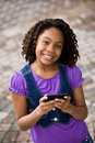 Elementary age young lady sending text message african american girl holding cellphone Royalty Free Stock Photos