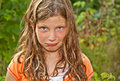Elementary aged caucasian girl playing outdoors making goof pouty face her hair tangled wind blown has piercing green eyes Royalty Free Stock Images