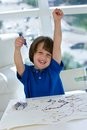 Elementary boy with fist in air drawing caucasian and marker hand art work on table Royalty Free Stock Image
