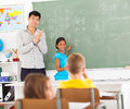 Elementary chinese applauding school teacher after young girl wrote words on blackboard Royalty Free Stock Photo