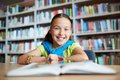 Elementary learner portrait of cheerful schoolgirl looking at camera while sitting in library Royalty Free Stock Photo