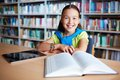 Elementary learner portrait of cheerful schoolgirl looking at camera while sitting in library Stock Photo