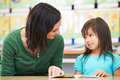 Elementary pupil reading with teacher in classroom looking at each other smiling Royalty Free Stock Image