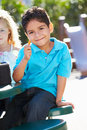 Elementary pupil sitting at table eating lunch looking camera Stock Photo