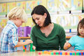 Elementary pupils counting with teacher in classroom using colourful blocks concentrating Stock Photography