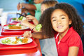 Elementary pupils enjoying healthy lunch in cafeteria holding fork smiling Royalty Free Stock Photography