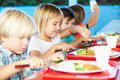 Elementary pupils enjoying healthy lunch in cafeteria sitting down using knife and fork Royalty Free Stock Image
