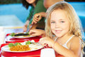Elementary pupils enjoying healthy lunch in cafeteria smiling at camera Stock Images
