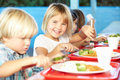Elementary pupils enjoying healthy lunch in cafeteria smiling at camera sitting down Stock Photos
