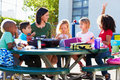Elementary pupils and teacher eating lunch outdoors sitting around table Stock Images
