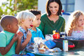 Elementary pupils and teacher eating lunch outdoors sitting down Stock Image