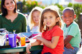 Elementary pupils and teacher eating lunch outdoors sitting at table smiling Royalty Free Stock Photos