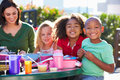 Elementary pupils and teacher eating lunch smiling at camera Royalty Free Stock Image