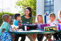 Elementary pupils and teacher eating lunch talking to each other outdoors Royalty Free Stock Images