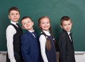 Elementary school boy friends, fooling around near blank chalkboard background, dressed in classic black suit, group pupil, educat Royalty Free Stock Photo