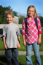 Elementary school kids an early morning shot of two little typical wearing backpacks Stock Image