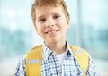 Elementary school learner portrait of cheerful schoolboy with backpack looking at camera Stock Images