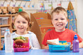 Elementary School Pupils With Healthy And Unhealthy Lunch Boxes Royalty Free Stock Photo